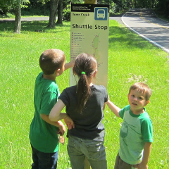 Kids reading a bus stop sign